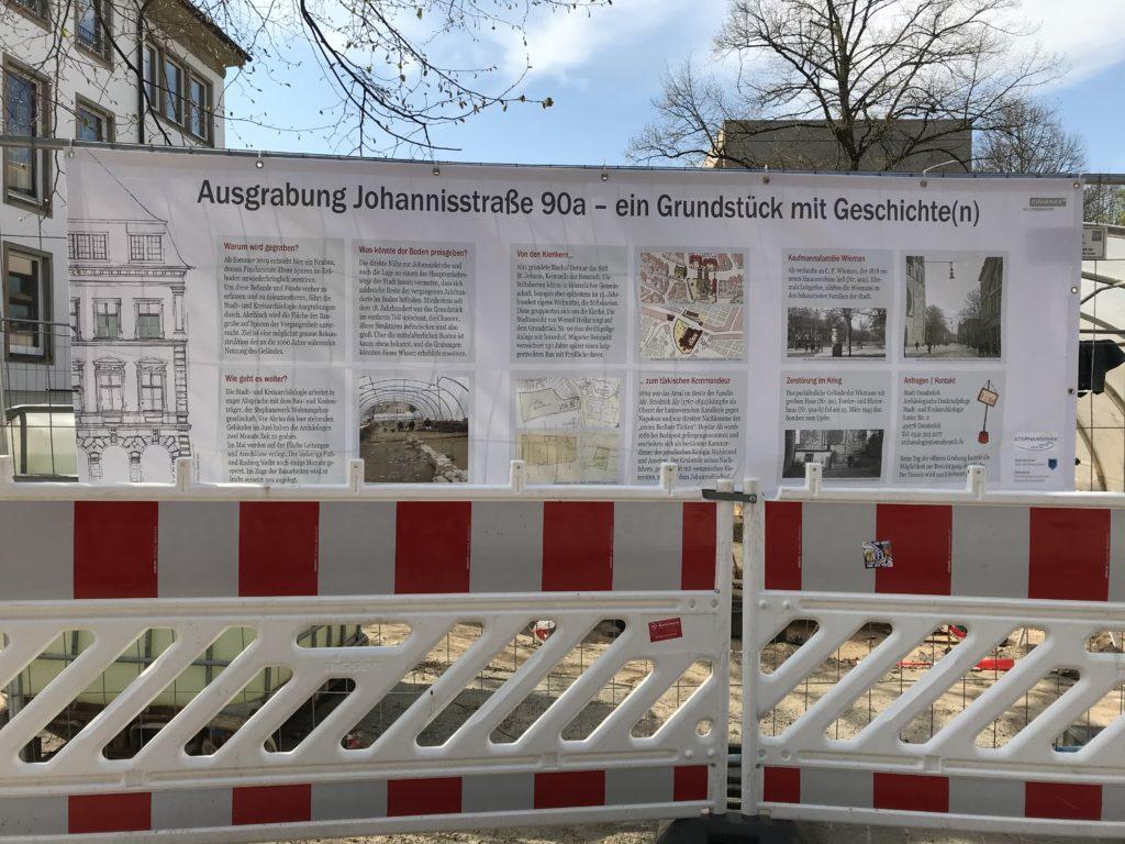 Am Bauzaun um das Grundstück Johannisstraße 90a hängt ein großes Banner mit Texten und Bildern zur Geschichte des Grundstücks.